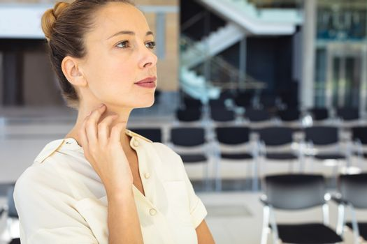 Side view of young Caucasian female executive looking away while standing in empty conference room