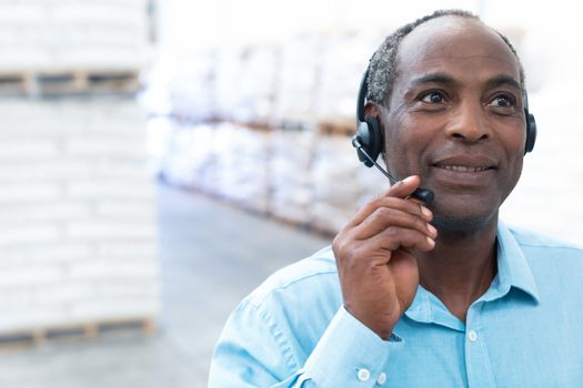 Portrait close-up of handsome mature African-american male supervisor talking on headset in warehouse. This is a freight transportation and distribution warehouse. Industrial and industrial workers concept