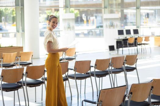 Side view of young Caucasian female executive looking at documents while standing in empty conference room