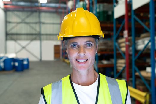 Front view of Happy Caucasian female staff looking at camera in warehous. This is a freight transportation and distribution warehouse. Industrial and industrial workers concept