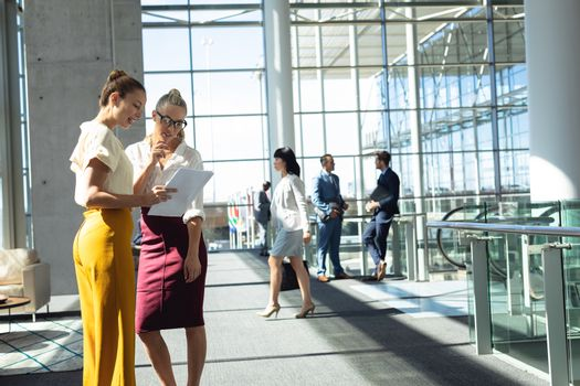 Side view of Caucasian female executives looking at documents while standing in modern office