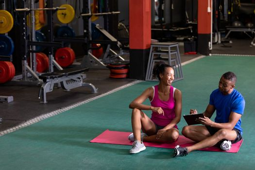 Front view of an African-American woman smiling while sitting crossed legged and an African-American man showing her results inside a room at a sports center. Bright modern gym with fit healthy people working out and training. Bright modern gym with fit healthy people working out and training