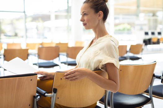 side view of young Caucasian female executive looking away while sitting on chair in empty conference room