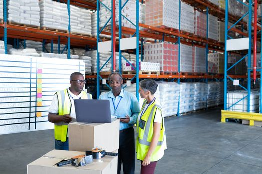 Warehouse staffs discussing over laptop in warehouse