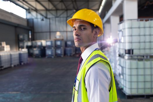 Portrait of African-american male staff in hardhat and reflective jacket standing in warehouse. This is a freight transportation and distribution warehouse. Industrial and industrial workers concept