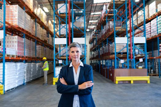 Front view of beautiful mature Caucasian female manager standing with arms crossed and looking at camera in warehouse. African-american colleague working in the background. This is a freight transportation and distribution warehouse. Industrial and industrial workers concept