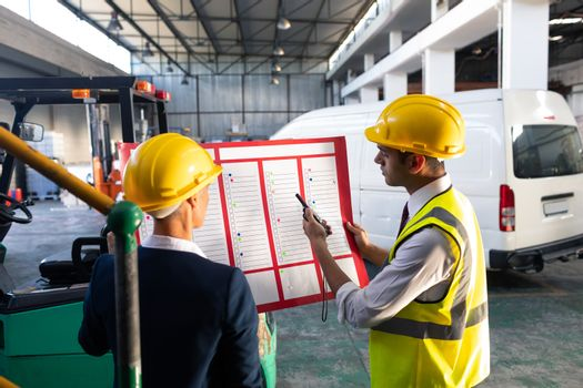 Rear view of Caucasian female manager and Caucasian male supervisor discussing over inventory chart in warehouse. This is a freight transportation and distribution warehouse. Industrial and industrial workers concept