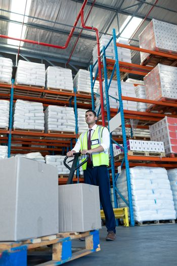 Low angle view of Caucasian male staff using pallet jack in warehouse. This is a freight transportation and distribution warehouse. Industrial and industrial workers concept