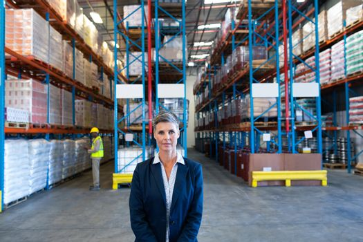Front view of beautiful mature Caucasian female manager looking at camera in warehouse. African-american colleague working in the background. This is a freight transportation and distribution warehouse. Industrial and industrial workers concept