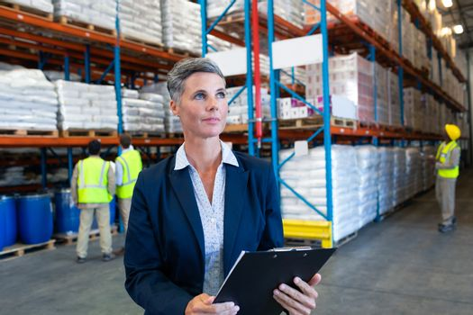 Front view of confident mature Caucasian female manager checking stocks on clipboard in warehouse. Diverse colleagues working in the background. This is a freight transportation and distribution warehouse. Industrial and industrial workers concept