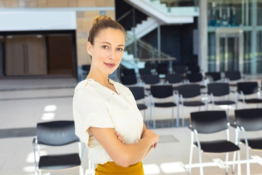 Front view of young Caucasian female executive looking at camera while standing in empty conference room