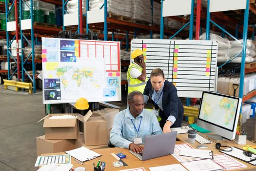 Front view of mature Caucasian female manager and African-american male supervisor discussing over laptop at desk in warehouse. This is a freight transportation and distribution warehouse. Industrial and industrial workers concept