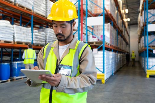 Front view of handsome mature Asian male worker working on digital tablet in warehouse. Diverse colleagues working in the background. This is a freight transportation and distribution warehouse. Industrial and industrial workers concept