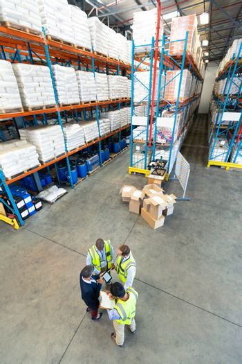 High angle view of diverse warehouse staff discussing over digital tablet in warehouse. This is a freight transportation and distribution warehouse. Industrial and industrial workers concept