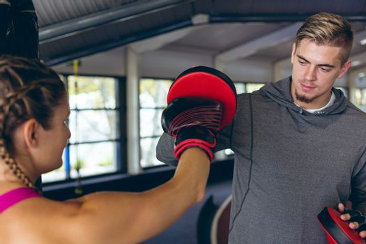 Close-up of fit Caucasian male trainer giving boxing training to pretty Caucasian female athletic. Bright modern gym with fit healthy people working out and training