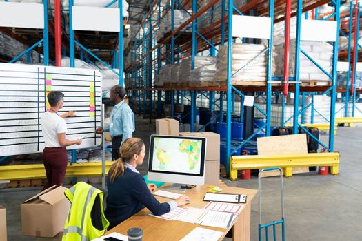 High angle view of mature female manager working on computer while coworkers discussing over whiteboard in warehouse. This is a freight transportation and distribution warehouse. Industrial and industrial workers concept