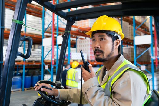 Portrait close-up of mature Caucasian male worker talking on walkie-talkie while driving forklift in warehouse. This is a freight transportation and distribution warehouse. Industrial and industrial workers concept