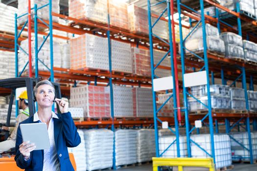 Front view of beautiful mature Caucasian female manager with digital tablet talking on headset in warehouse. Asian coworker sitting on forklift. This is a freight transportation and distribution warehouse. Industrial and industrial workers concept