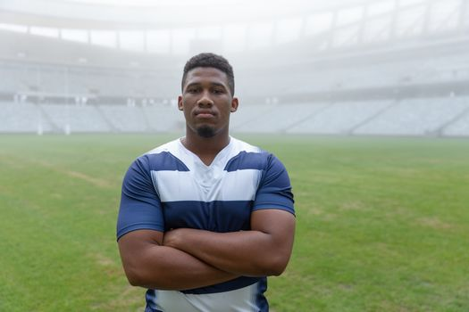 Portrait of African american rugby player standing with arms crossed in the stadium