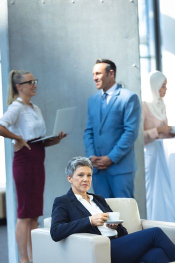 Front view of mature businesswoman drinking coffee and looking away in modern office. Behind her, colleagues interacting with each other.