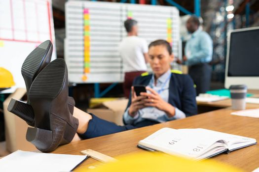 Front view of mature Caucasian female manager relaxing with feet up while using mobile phone at desk in warehouse. Diverse colleagues discussing in the background. This is a freight transportation and distribution warehouse. Industrial and industrial workers concept