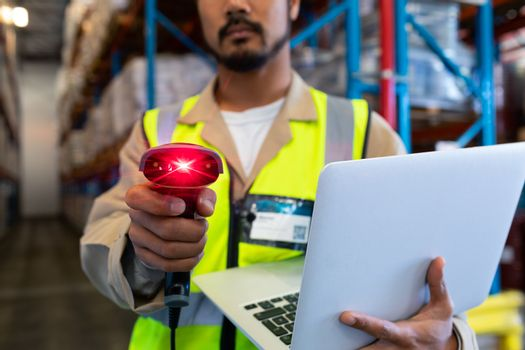 Mid section of Asian mature male worker with laptop showing barcode scanner on camera in warehouse. This is a freight transportation and distribution warehouse. Industrial and industrial workers concept