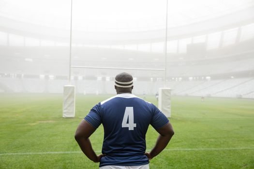 Rear view of African american male rugby player standing with hands on hip in stadium