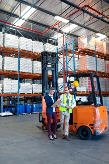 Front view of mature Caucasian male and female staff working together near forklift in warehouse. This is a freight transportation and distribution warehouse. Industrial and industrial workers concept