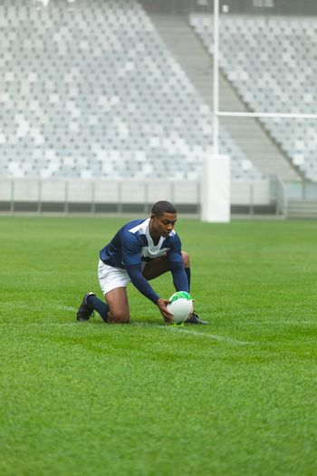 Front view of African American male rugby player placing rugby ball on the stand in stadium