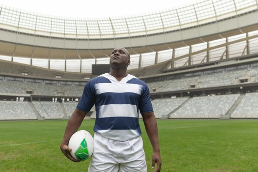 Front view of African American rugby player standing with rugby ball and looking up in stadium
