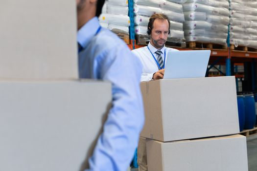 Front view of handsome mature Caucasian male supervisor with headset working on laptop in warehouse. Asian male worker holding cardboard boxes on the foreground. This is a freight transportation and distribution warehouse. Industrial and industrial workers concept