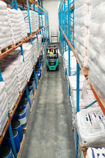 High angle view of African-american male worker driving forklift in warehouse. This is a freight transportation and distribution warehouse. Industrial and industrial workers concept