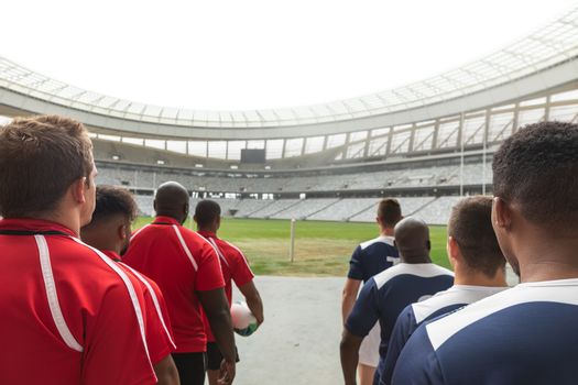 Rear view of rugby teams standing in a row at the entrance of stadium for match