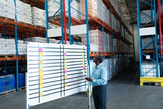 Side view of handsome mature African American male supervisor looking at whiteboard in warehouse. This is a freight transportation and distribution warehouse. Industrial and industrial workers concept