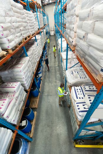High angle of diverse warehouse staff checking stocks in aisle in warehouse. They are holding clipboards and writing in it. This is a freight transportation and distribution warehouse. Industrial and industrial workers concept