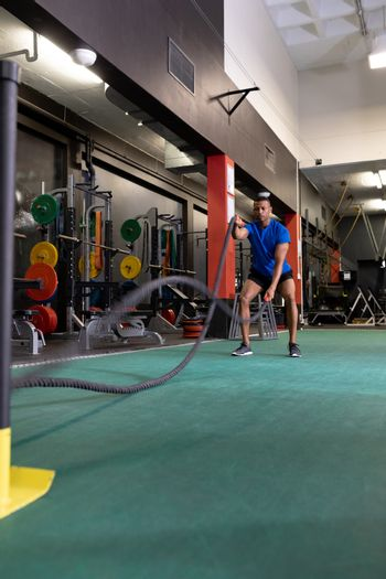 Front view of an African-American man doing battle rope exercises inside a room at a sports centre. Bright modern gym with fit healthy people working out and training. Bright modern gym with fit healthy people working out and training