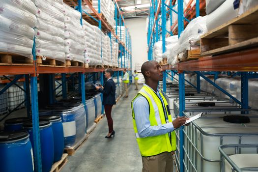 Side view of diverse warehouse staff checking stocks in aisle in warehouse. They are holding clipboards and writing in it. This is a freight transportation and distribution warehouse. Industrial and industrial workers concept