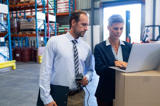 Front view of mature Caucasian staffs working together on laptop in warehouse. This is a freight transportation and distribution warehouse. Industrial and industrial workers concept