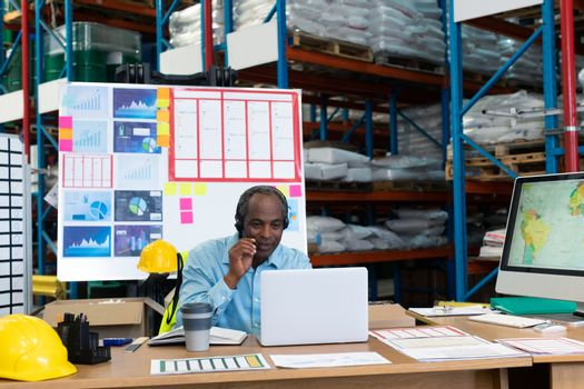 Front view of mature African american male supervisor talking on headset while using laptop at desk in warehouse. This is a freight transportation and distribution warehouse. Industrial and industrial workers concept