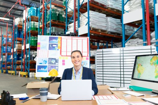 Portrait of beautiful young Caucasian female manager using laptop at desk in warehouse. This is a freight transportation and distribution warehouse. Industrial and industrial workers concept