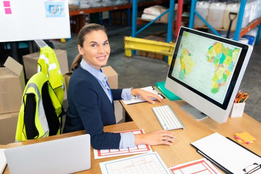 Portrait of beautiful young Caucasian female manager working on computer at desk in warehouse. This is a freight transportation and distribution warehouse. Industrial and industrial workers concept