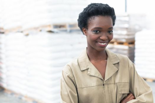 Portrait close-up of pretty African-america female worker standing with arms crossed and looking at camera in warehouse. This is a freight transportation and distribution warehouse. Industrial and industrial workers concept
