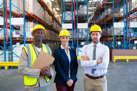 Front view of confident diverse staffs looking at camera in warehouse. This is a freight transportation and distribution warehouse. Industrial and industrial workers concept