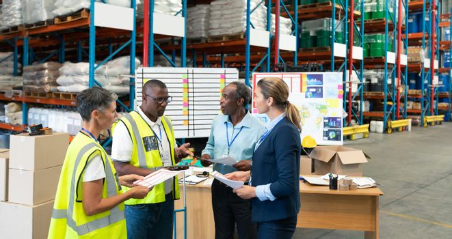 Front view of mature diverse staffs discussing over document in warehouse. This is a freight transportation and distribution warehouse. Industrial and industrial workers concept