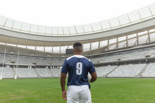 Rear view of African American rugby player standing with rugby ball in stadium