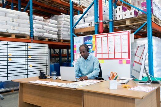 Front view of mature African-american male supervisor working on laptop at desk in warehouse. This is a freight transportation and distribution warehouse. Industrial and industrial workers concept