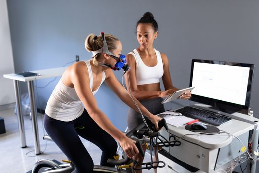 Side view of a Caucasian athletic woman doing a fitness test using a mask connected to a monitor while riding an exercise bike  and an African-American woman monitoring her results inside a room at a sports center. Bright modern gym with fit healthy people working out and training. Athlete testing themselves with cardiovascular fitness test on exercise bike