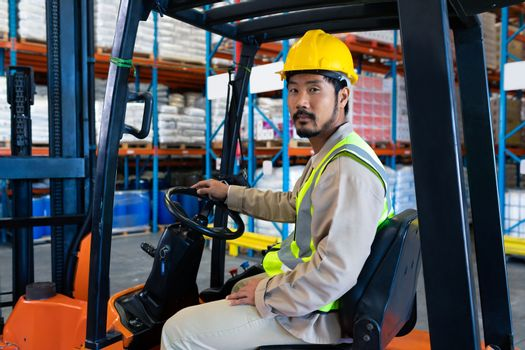 Portrait of confident mature Asian male worker sitting in forklift and looking at camera in warehouse. This is a freight transportation and distribution warehouse. Industrial and industrial workers concept