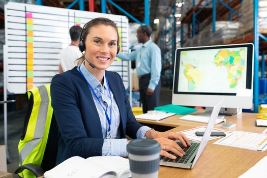 Front view of mature Caucasian female manager with headset using laptop at desk in warehouse. In the background diverse coworkers are discussing in front of whiteboard. This is a freight transportation and distribution warehouse. Industrial and industrial workers concept
