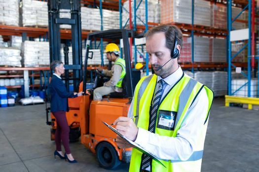 Front view of handsome Caucasian male supervisor with headset writing on clipboard in warehouse. Diverse colleagues working in the background. This is a freight transportation and distribution warehouse. Industrial and industrial workers concept